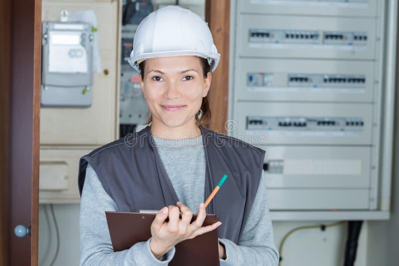 Portret vrouwelijke elektricien met klembord bij fusebox stock fotografie
