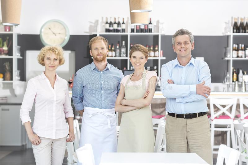 Portret właściciele i pięcioliniowa pozycja przeciw kontuarowi w restauracji obraz royalty free