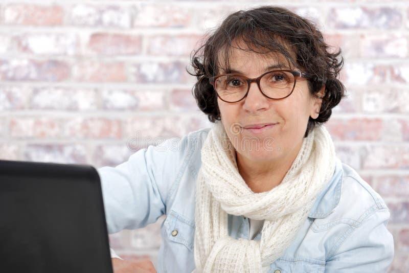 Portret w średnim wieku kobieta używa laptop zdjęcie stock