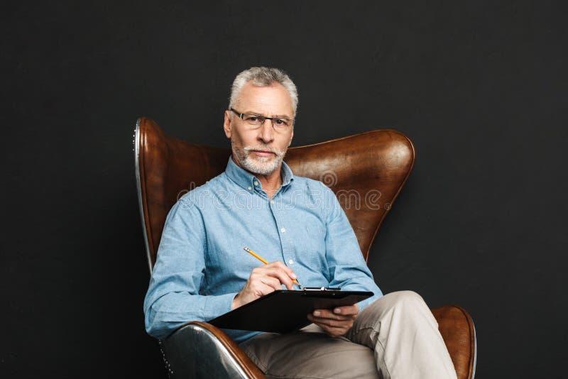 Portret w średnim wieku mężczyzna 60s z popielatym włosy i brody obsiadaniem zdjęcie royalty free