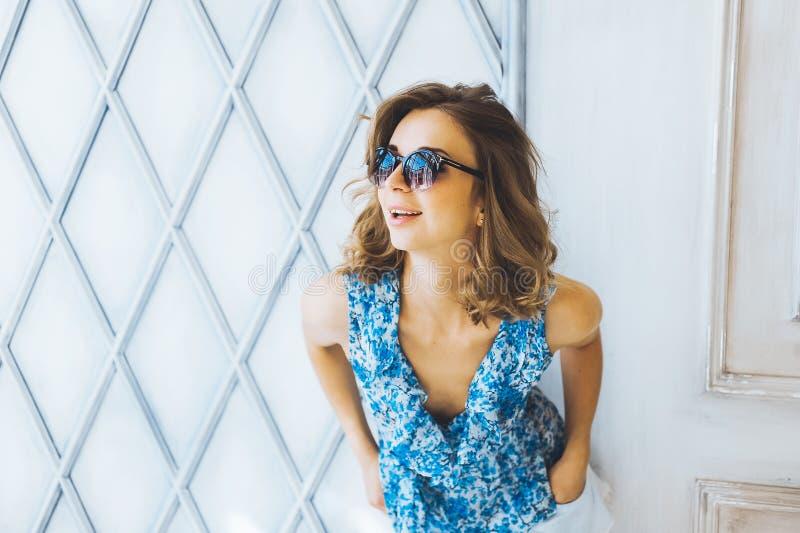 Portret w pracownianej pięknej młodej kędzierzawej dziewczynie w okularach przeciwsłonecznych, krótkich drelichów skrótach i błęk zdjęcia stock