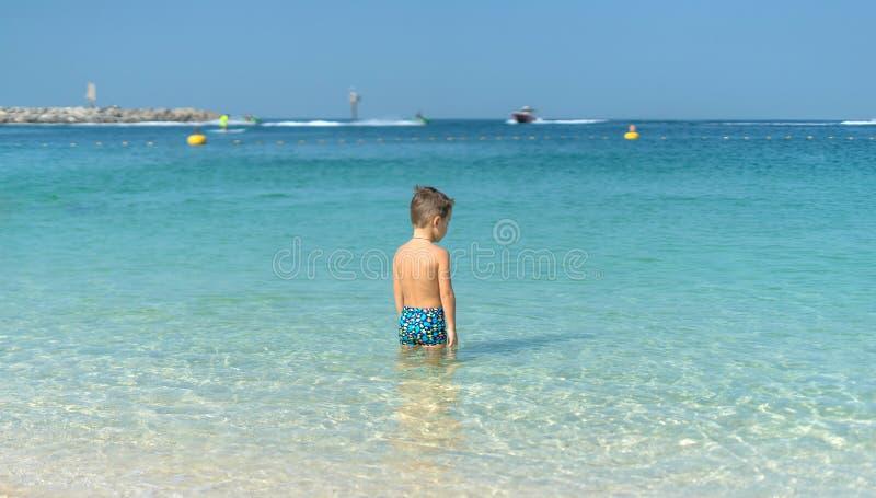 Portret weinig jongen die in het overzees, oceaan spelen Gelukkige familie die pret op tropisch wit strand hebben Positieve mense royalty-vrije stock afbeelding