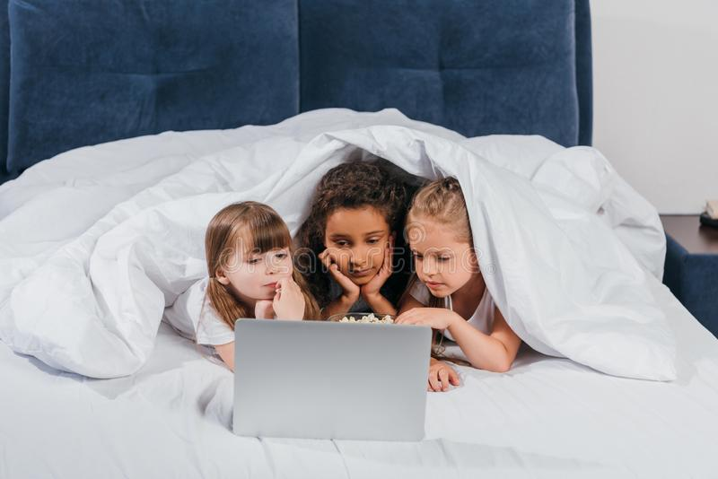 portret wieloetniczne skoncentrowane dziewczyny używa laptop podczas gdy odpoczywający zdjęcia stock