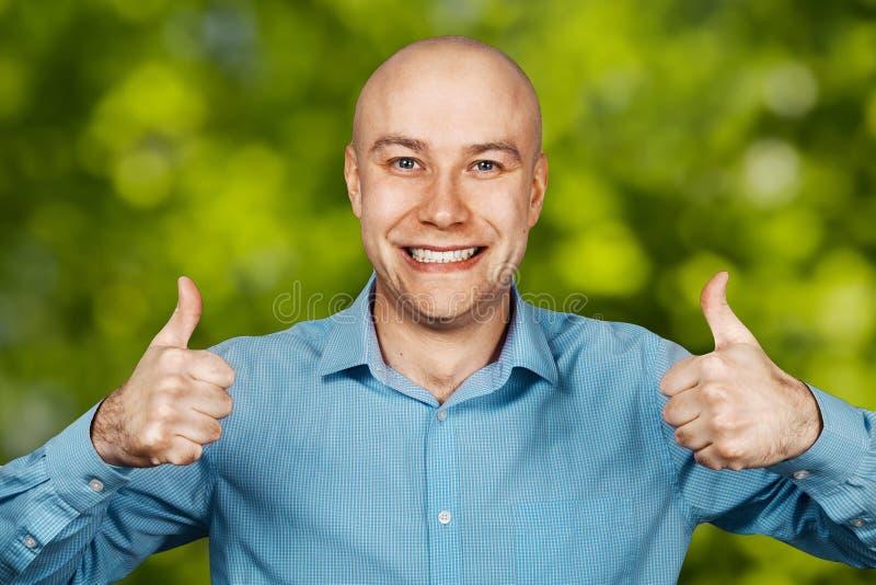 Portret Witte kale kerel in blauw overhemd op duimen tonen en gras groene achtergrond die glimlachen royalty-vrije stock foto's