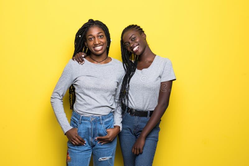Portret wpólnie odizolowywający nad żółtym tłem dwa uśmiechniętej młodej afrykańskiej kobiety stoi zdjęcia stock