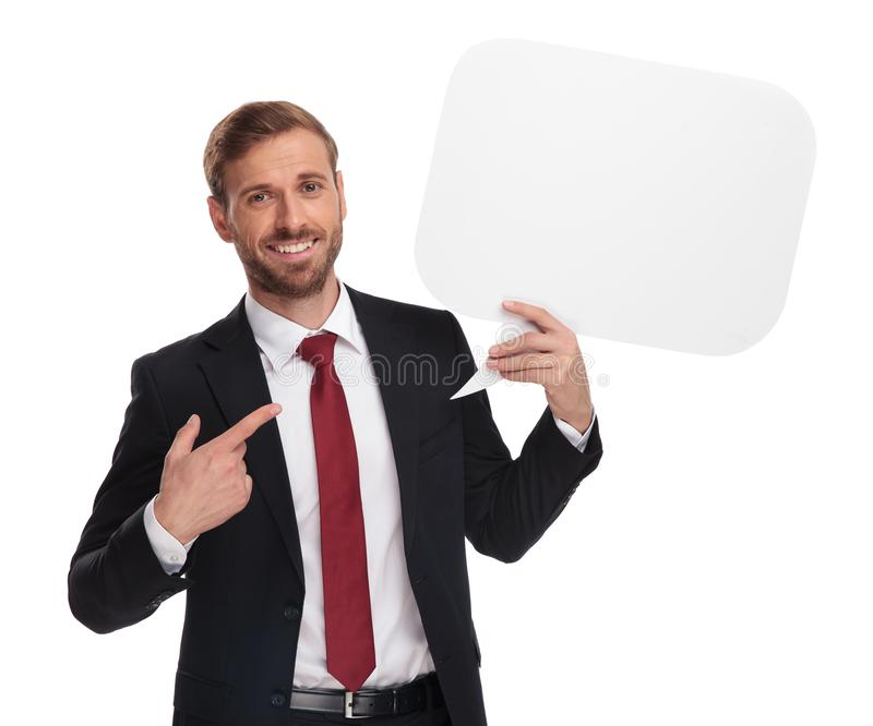 Portret wskazuje przy białym mowa bąblem szczęśliwy biznesmen obrazy stock