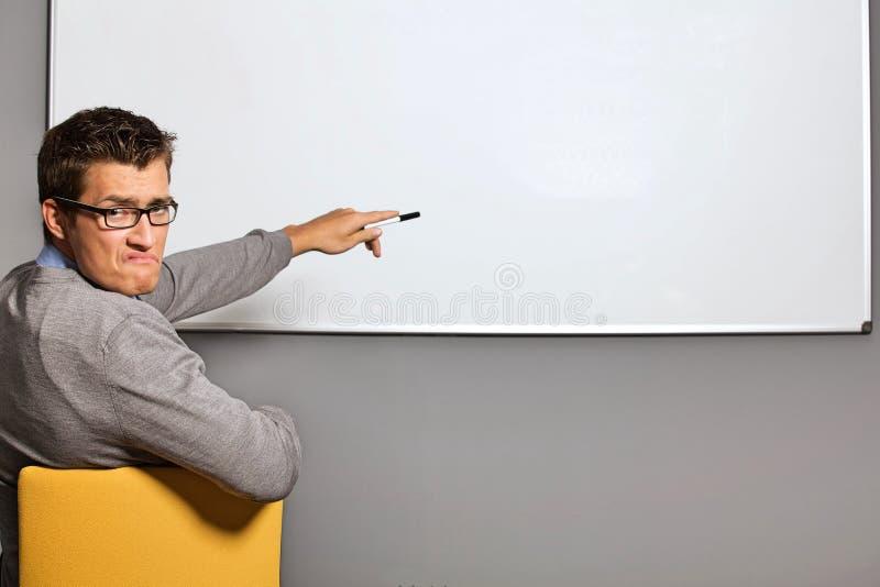 Portret wskazuje przy whiteboard i robi twarzy w biurze biznesmen obrazy stock