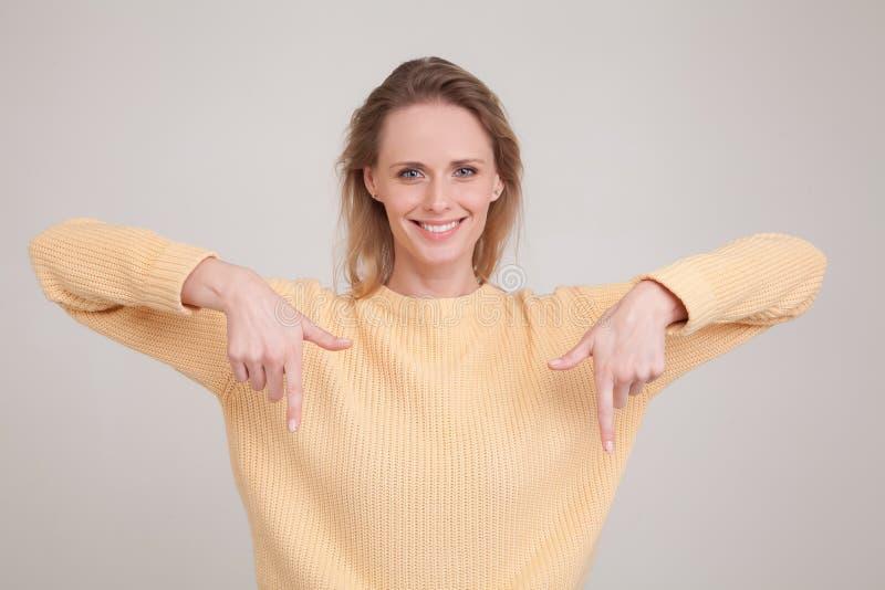 Portret wskazuje w dół blondynki kobieta gdy ono uśmiecha się życzliwy przy kamerą proponuje próba produktu ot wp8lywy spojrzenie zdjęcia stock