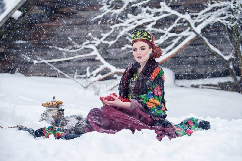 Portret wspaniała młoda kobieta w rosjanina stylu sukni na silnym mrozie w zima śnieżnym dniu z jabłkami i samowarem fotografia royalty free