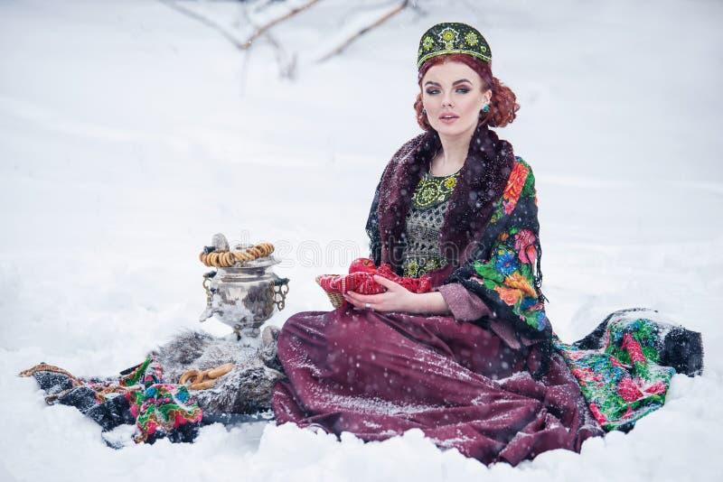Portret wspaniała młoda kobieta w rosjanina stylu sukni na silnym mrozie w zima śnieżnym dniu z jabłkami i samowarem zdjęcie stock