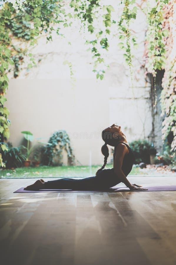 Portret wspaniałej młodej kobiety ćwiczy joga salowy Piękny dziewczyny praktyki kobry asana w klasie Calmness i relaksuje zdjęcia royalty free