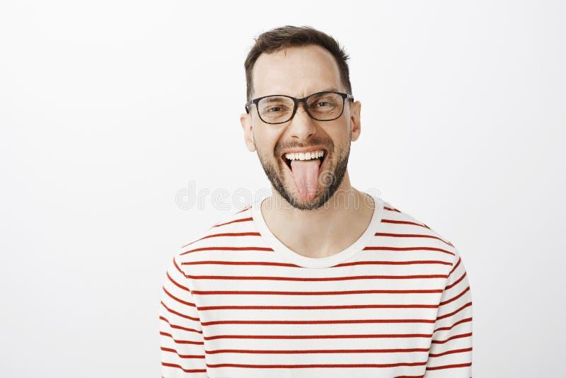 Portret wtyka out jęzor i ono uśmiecha się joyfully atrakcyjny śmieszny dorosły coworker w czarnych szkłach, być beztroski obraz royalty free