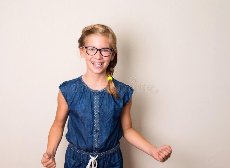 Portret wygrywa pomyślnej nastolatek dziewczyny w eyeglasses i brac fotografia stock