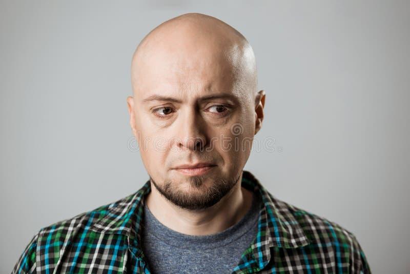 Portret wzburzony przystojny mężczyzna myśleć nad beżowym tłem zdjęcie stock