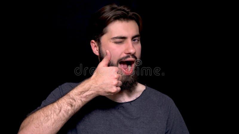 Portret z podnieceniem mężczyzna z rozpieczętowanym usta daje aprobatom i mruga przeciw czarnemu tłu Uśmiechnięci brodaci potomst obrazy royalty free