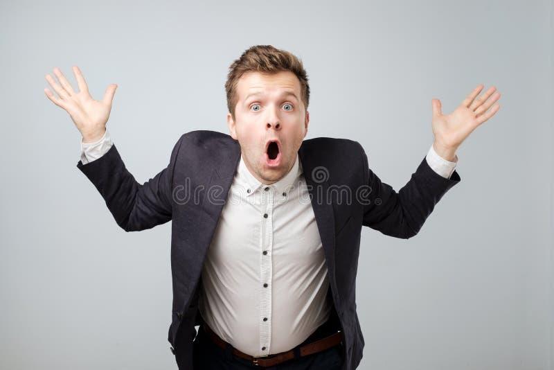 Portret z podnieceniem młoda samiec krzyczy w szoka i zdumienia mieniu w kostiumu wręcza up zdjęcia royalty free