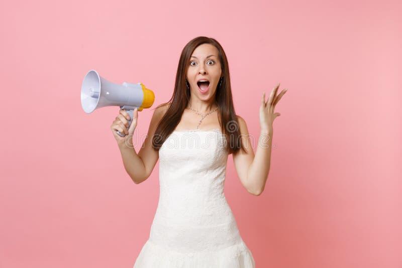 Portret z podnieceniem panny młodej kobieta z rozpieczętowanym usta w ślubnej sukni mienia megafonie, podesłanie ręki na menchiac obrazy royalty free