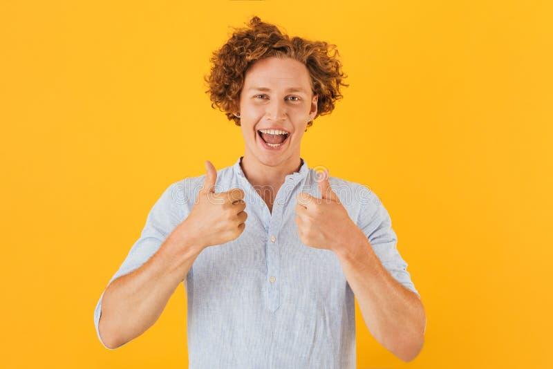 Portret z podnieceniem przystojny facet 20s uśmiecha się kciuki i pokazuje zdjęcie stock