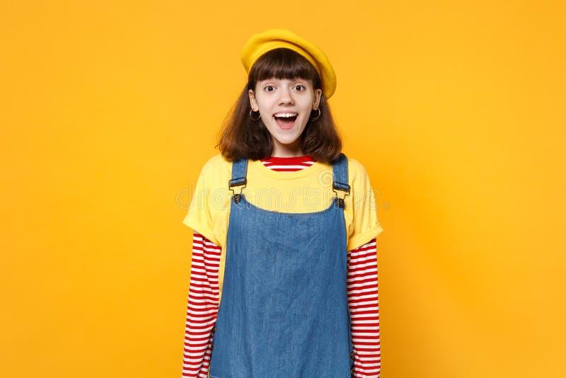 Portret z podnieceniem rozochocony śmieszny dziewczyna nastolatek w francuskim berecie, drelichowy sundress stać odizolowywam na  zdjęcia stock