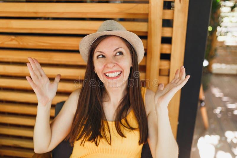 Portret z podnieceniem uśmiechnięta młoda kobieta w słomianym lato kapeluszu, żółte koszulowe podesłanie ręki na drewnianym tle w obrazy royalty free