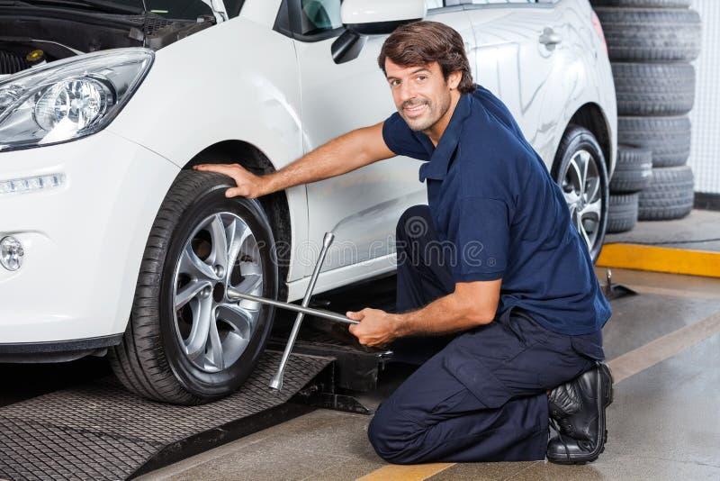 Portret Załatwia Samochodową oponę Przy garażem mechanik fotografia royalty free