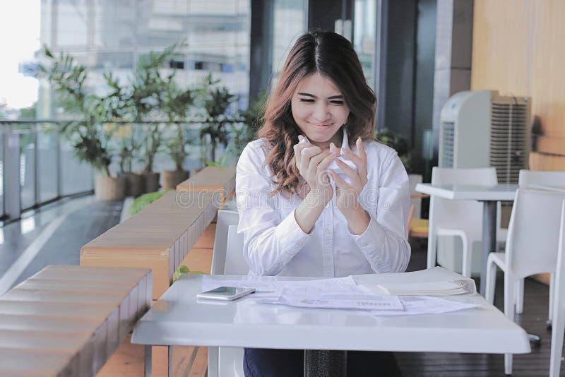 Portret zaakcentowana młoda Azjatycka biznesowa kobieta miie prześcieradła papier przy biurkiem w biurze zdjęcie stock