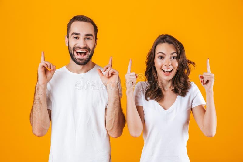 Portret zadowoleni ludzie obsługuje i kobieta wskazuje palce w podstawowej odzieży, podczas gdy stojący wpólnie odizolowywa nad k zdjęcia stock