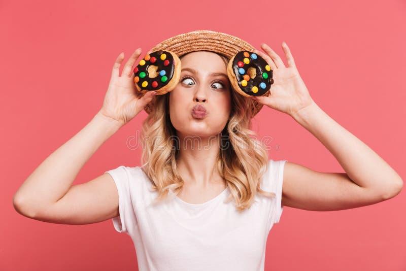 Portret zadowolona blond kobieta 20s jest ubranym s?omianego kapelusz ?mia si? podczas gdy trzymaj?cy smakowitych s?odkich donuts zdjęcie royalty free