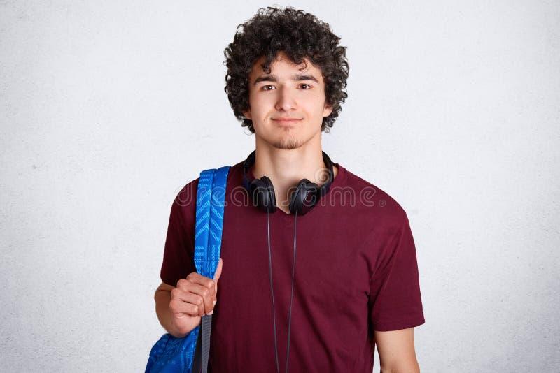 Portret zadowolonego modnisia męski uczeń z chrupiącym włosy, jest ubranym przypadkową t koszula, niesie plecaka, hełmofony na sz zdjęcie stock