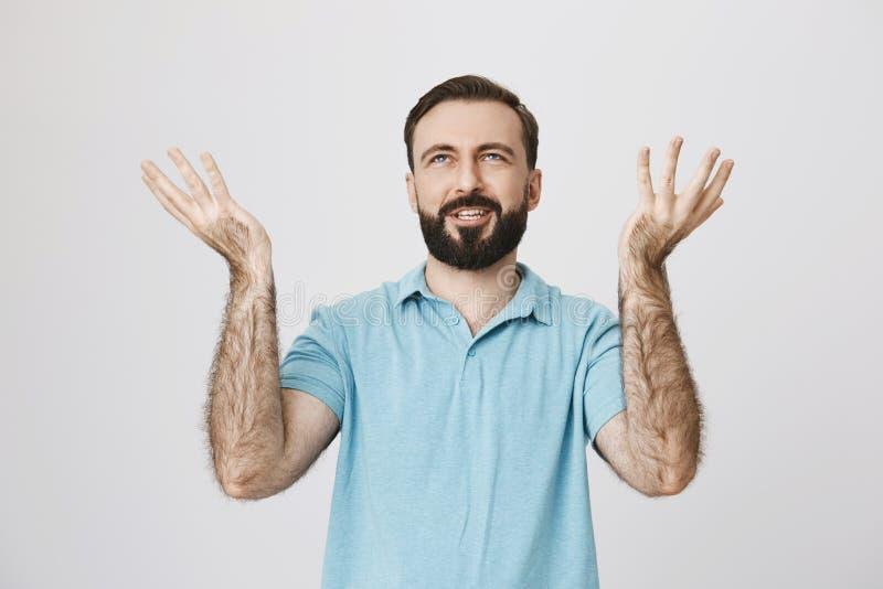 Portret zadowolony brodaty mężczyzna trzyma jego palmy up odizolowywać na białym tle Wielki, deszcz Jaki inny może to zdjęcie stock