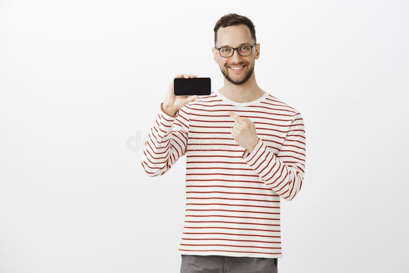 Portret zadowolony imponujący śliczny sklepu klient z szczecina w czarnym modnym eyewear, trzyma smartphone w horyzontalnym obraz stock