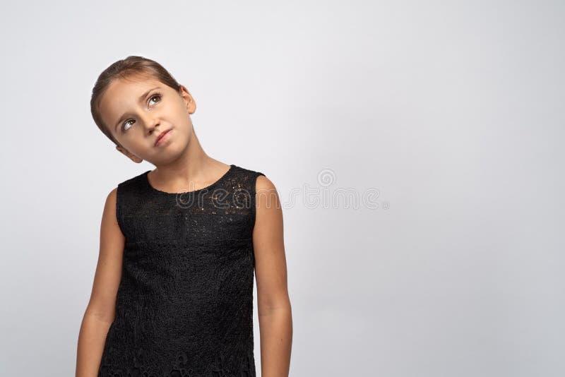 Portret zadumana ładna dziewczyny brunetka w czarnej sukni Pięknego wątpliwego nierozstrzygającego dziecka przyglądający up rozwa zdjęcie royalty free