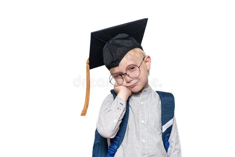 Portret zadumana blond chłopiec w dużych szkłach, akademickim kapeluszu i szkolnej torbie, Bia?y t?o isolate zdjęcia stock