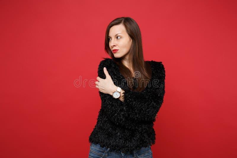Portret zadumana młoda kobieta w czarnym futerkowym puloweru mieniu wręcza krzyżuje, patrzejący na boku odizolowywający na jaskra zdjęcia stock