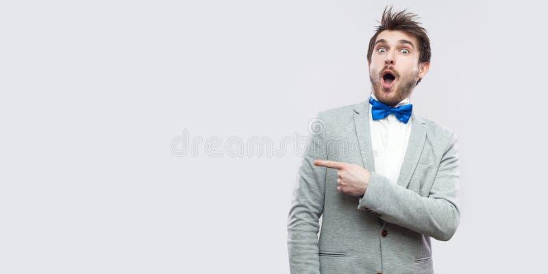 Portret zadziwiający przystojny brodaty mężczyzna stoi w przypadkowym siwieje kostium i błękitnego łęku krawat patrzejący kamerę  obrazy royalty free