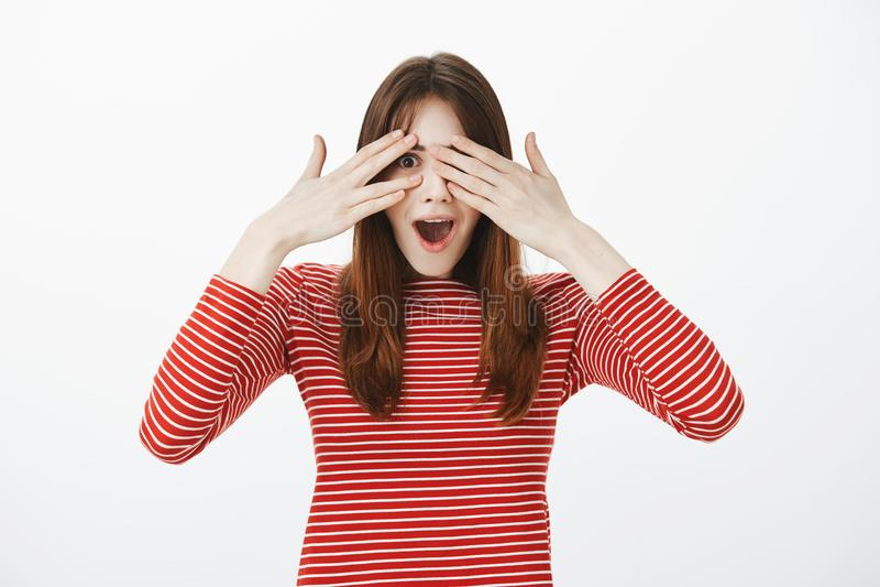 Portret zadziwiająca europejska dziewczyna w przypadkowych ubraniach, zakrywający oczy, zerkanie przez palców jest i zaskakujący  zdjęcia royalty free