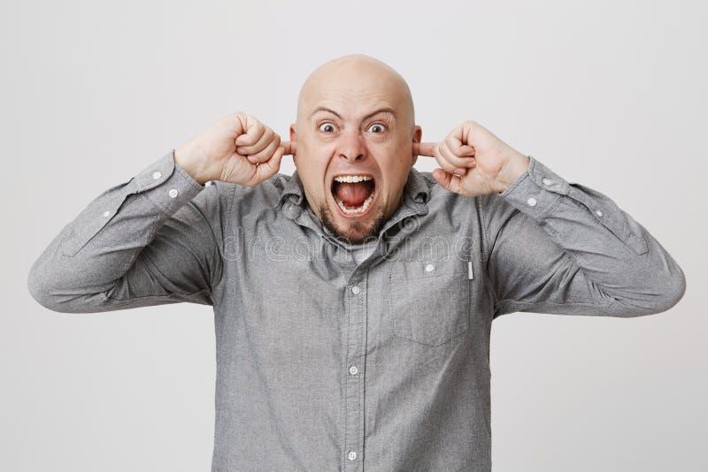 Portret zakrywa jego ucho krzyczy z palcami młody człowiek, wyraża stres nad białym tłem rozczarowany zdjęcie stock