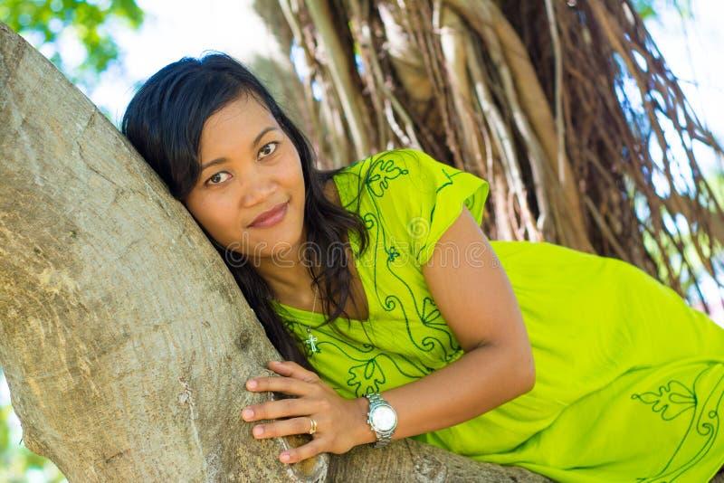 Portret zamknięty młoda piękna azjatykcia dziewczyna kłaść przy banyan drzewem patrzeje kamerę up fotografia royalty free