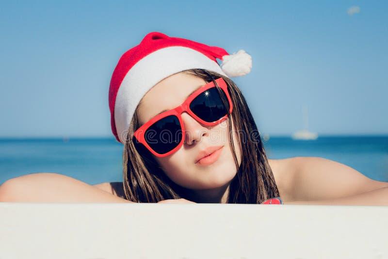 Portret zamknięty w górę ładnej nastoletniej dziewczyny w Święty Mikołaj kapeluszu fotografia royalty free