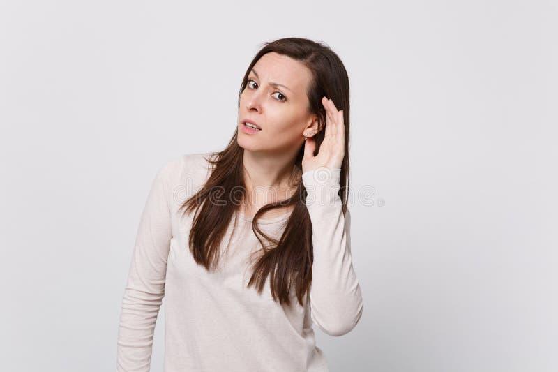Portret zaniepokojona młoda kobieta patrzeje kamerę w świateł ubraniach i podsłuchuje z przesłuchanie gestem na bielu zdjęcia royalty free