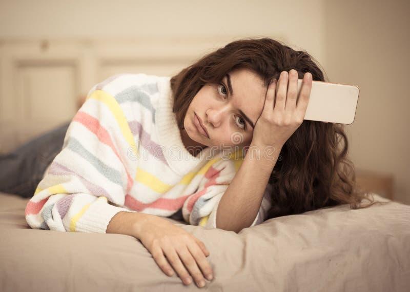 Portret zanudzająca, nieszczęśliwa i zmęczona ładna młoda dziewczyna używa m, fotografia royalty free