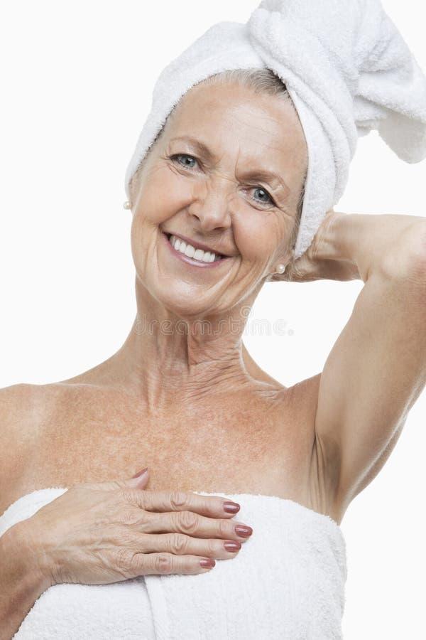 Portret zawijający w ręcznikach przeciw białemu tłu starsza kobieta fotografia royalty free