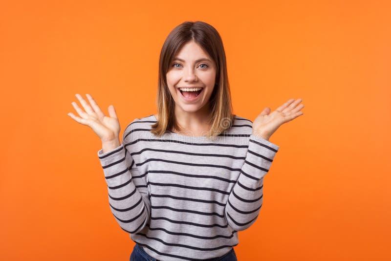 Portret zdumiewającej, pięknej młodej kobiety z brązowymi włosami w długiej rękawowej koszuli w prążkowanej kryty studio nakręcon zdjęcie stock