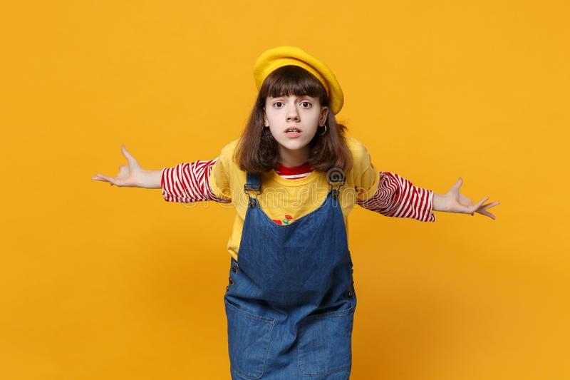 Portret zdumiony podrażniony dziewczyna nastolatek w francuskim berecie, drelichowi sundress rozprzestrzenia ręki odizolowywać na obraz stock