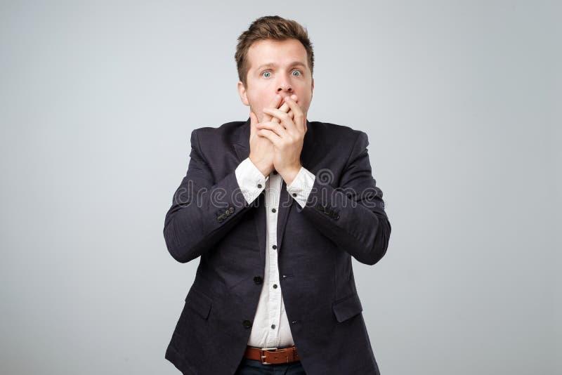Portret zdziweni młodzi człowiecy w kostiumu zakrywa jego usta ręką podczas gdy stać odizolowywam na popielatej ścianie fotografia royalty free