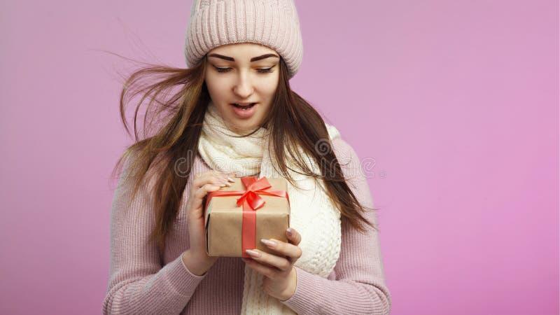 Portret zdziwiona dziewczyna z prezenta pudełkiem, młodą kobietą w trykotowym kapeluszu i szalikiem na różowym barwionym tle z te zdjęcie royalty free