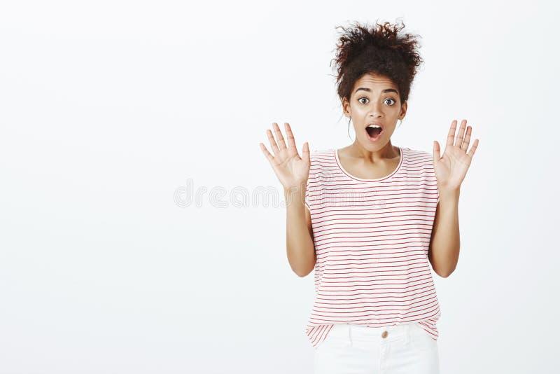 Portret zdziwiona i zadziwiająca piękna kobieta z rozczesanym kędzierzawym włosy, podnosi rozciągnięte palmy i dyszeć opuszcza sz zdjęcie stock