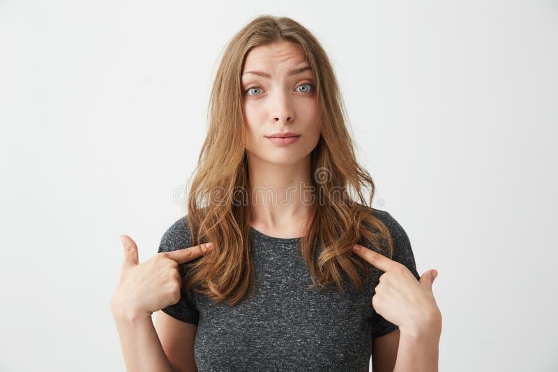Portret zdziwiona młoda piękna dziewczyna patrzeje kamerę wskazuje palce przy ona nad białym tłem obrazy stock