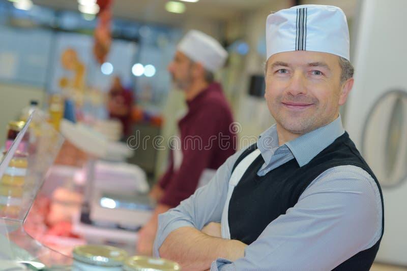 Portret zekere mannelijke slagers die in slachterij glimlachen stock afbeeldingen
