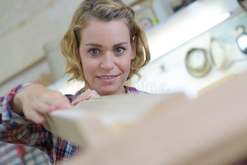 Portret zekere vrouwelijke timmerman die lade in workshop meten stock afbeelding